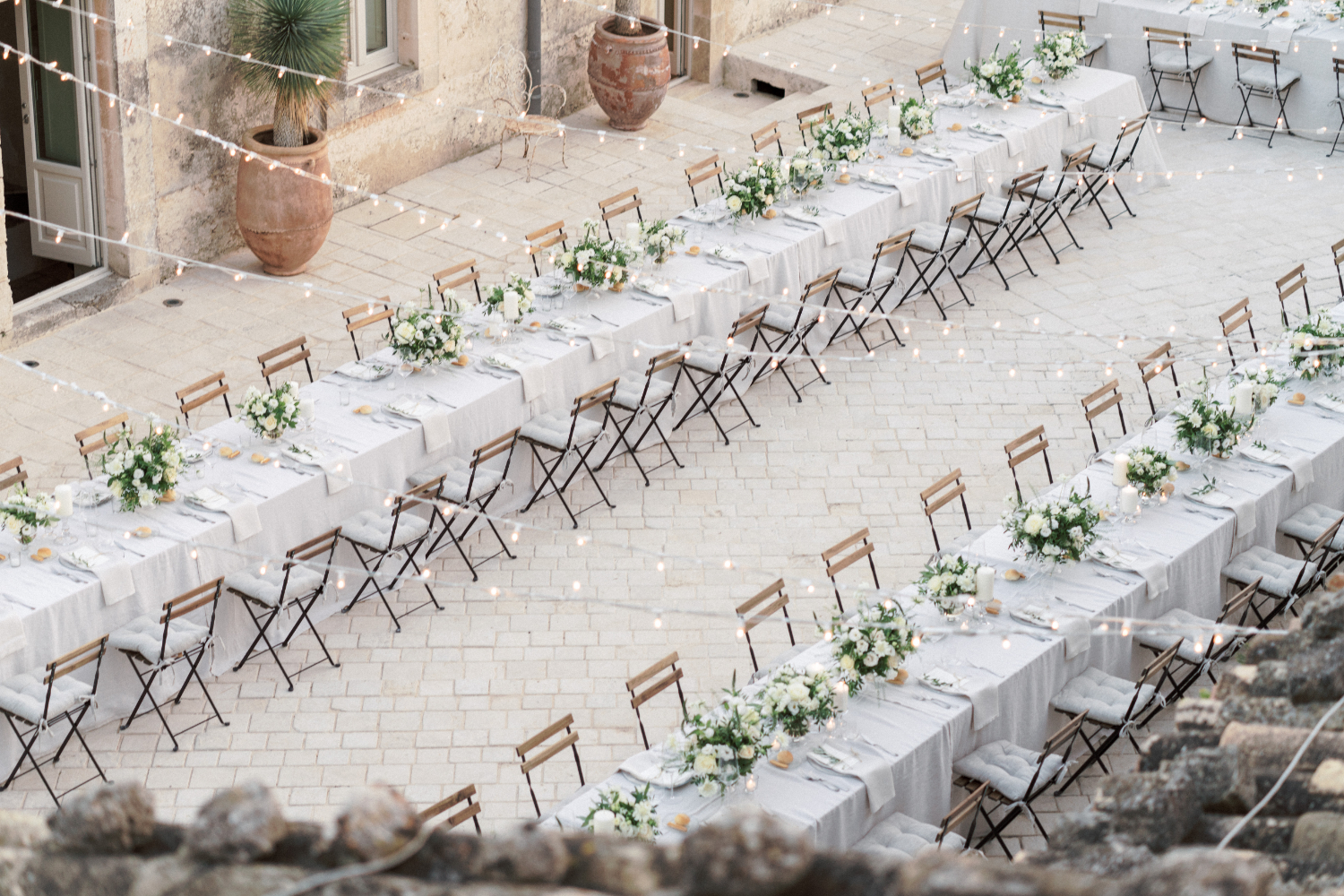 destination wedding in Italy - tuscany wedding venue decorated with fairy lights and long table for a wedding celebration